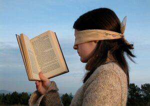 Lendo um livro com os olhos vendados.
